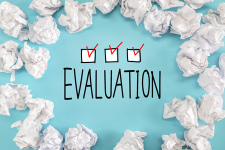Evaluation text with crumpled paper balls on a blue background Stock Photo