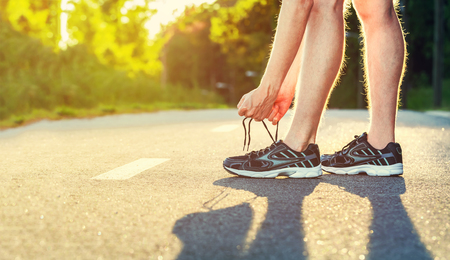 Male jogger tying his running shoes outside Stock Photo