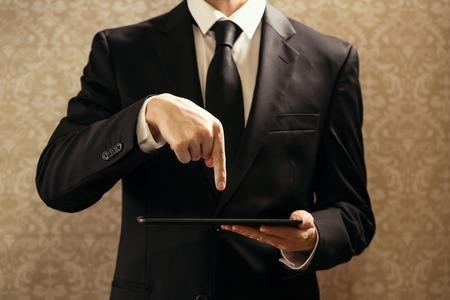 Businessman using a digital tablet on a dark background