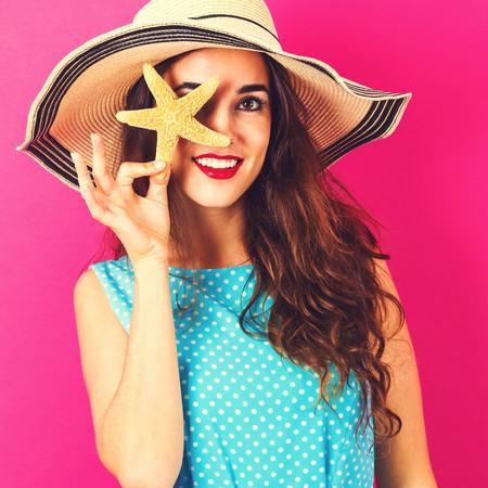 Gelukkige jonge vrouw die een zeester op een roze achtergrond houdt