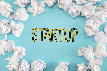 Startup text with crumpled paper balls on a blue background Banco de Imagens