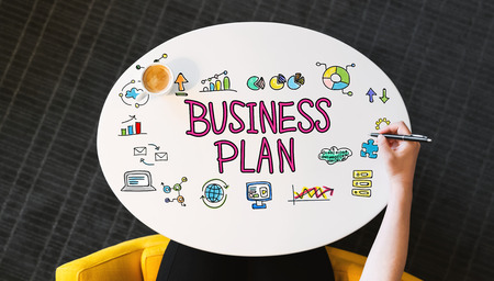 Business Plan text on a white table with person?s hand Stok Fotoğraf