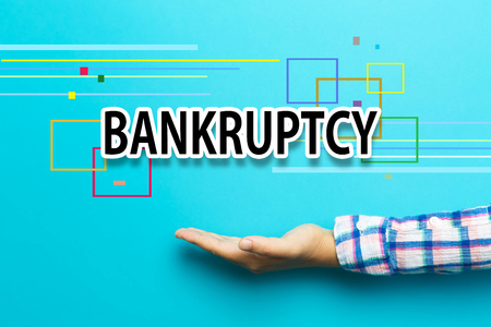 Bankruptcy concept with hand on blue background