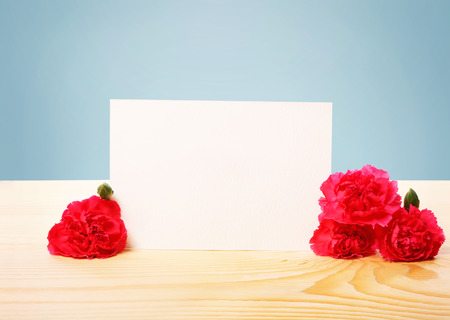 Blank Off White Greeting Card with Attractive Carnation Flowers on Top of a Wooden Table with Blue Background Stock Photo