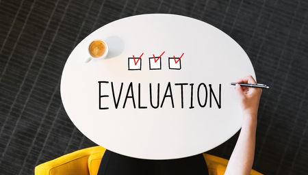 Evaluation text on a white table with person?s hand