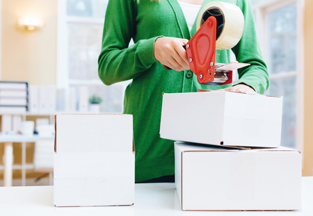 taping: Young woman packing boxes to be shipped in her home office