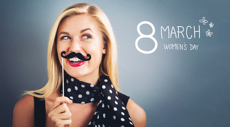 young womens: Womens Day text with young woman holding paper party sticks on a gray background Stock Photo
