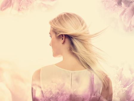 ピンクの花柄背景の美しい若い女性 写真素材