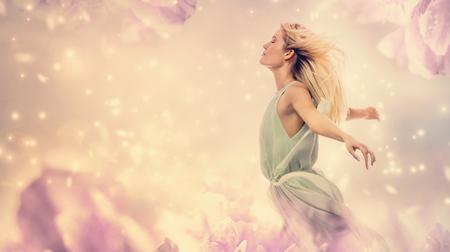 Mooie vrouw in een jurk in een roze pioenroos fantasie