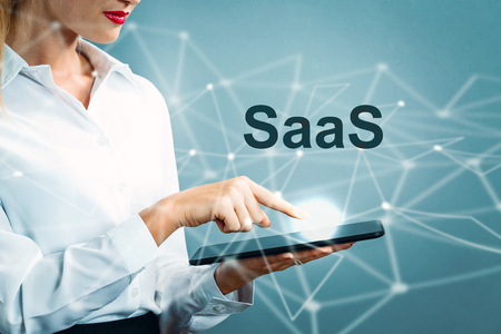 SaaS text with business woman using a tablet 스톡 콘텐츠