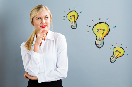 Light Bulbs with young business woman in a thoughtful pose
