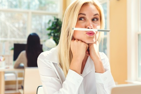 Young woman holding a pen above lips in an office Stock Photo