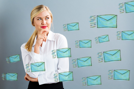 Emails with young business woman in a thoughtful pose Stock Photo