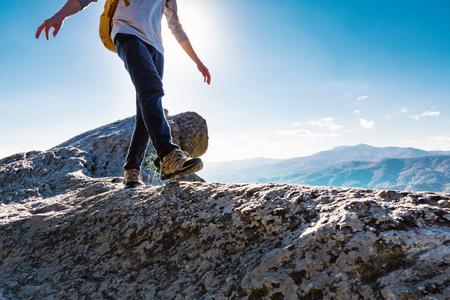 Man lopen op de rand van een klif hoog boven de bergen