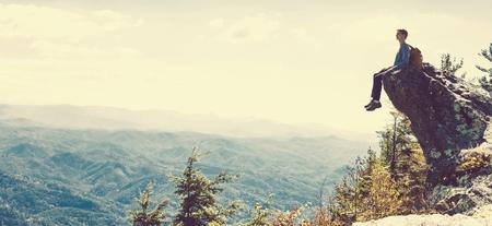 山々 を見下ろす崖の端に座っている男