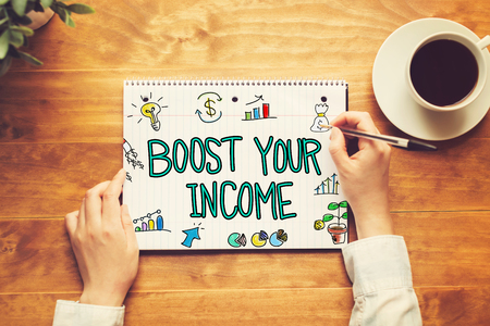 Boost Your Income text with a person holding a pen on a wooden desk