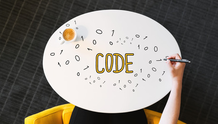 Code text on a white table with person?s hand Stock Photo