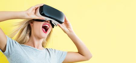 仮想現実のヘッドセットを使用して幸せな若い女 写真素材