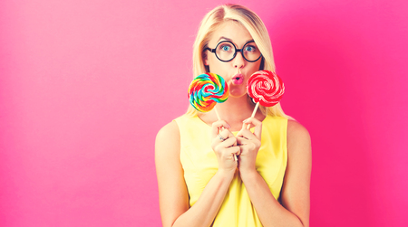 Young woman holding lollipop s on a pink background