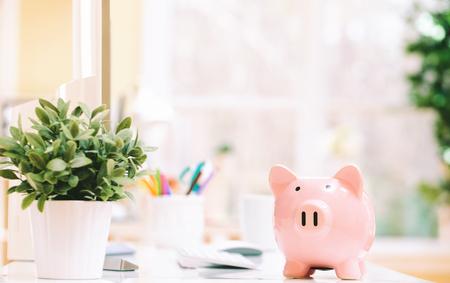 사무실에서 책상에 핑크 돼지 저금통