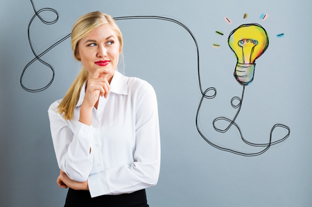 Light Bulb with young business woman in a thoughtful pose