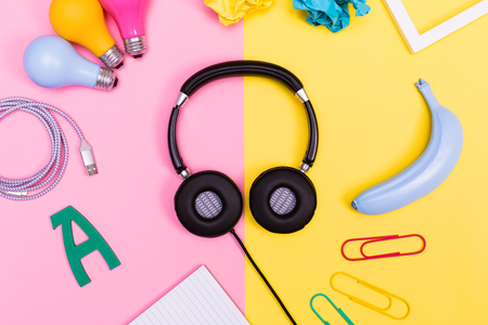Headphones with objects on a pink and yellow background Stock Photo