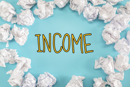 Income text with crumpled paper balls on a blue background