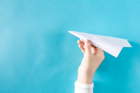 Hand holding a paper airplane on a blue background