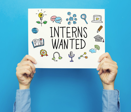 Interns Wanted text on a white poster on a blue background Stok Fotoğraf