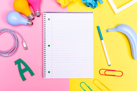 Notepad with objects on a pink and yellow background