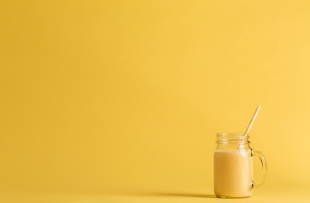 Smoothie in a mason jar on a yellow background Stock fotó - 77520208