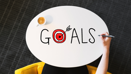 Goals text on a white table with a person holding a pen Stock Photo