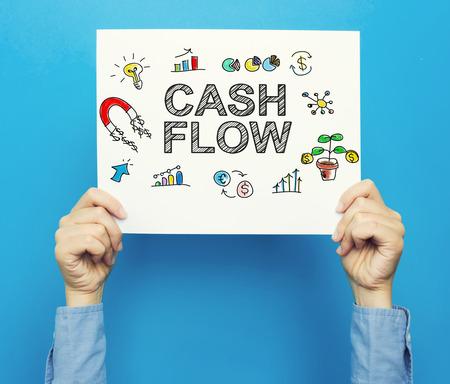 Cashflowtekst op een witte affiche op een blauwe achtergrond Stockfoto - 78026560