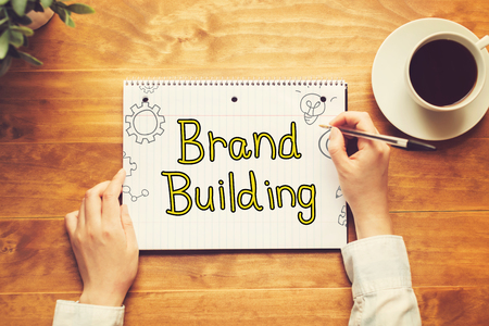 Brand Building text with a person holding a pen on a wooden desk Stock Photo