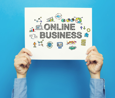 hand holding paper: Online Business text on a white poster on a blue background