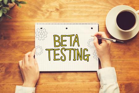 木製の机の上のペンを持つ人とベータ版テスト テキスト