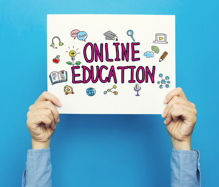 hand holding paper: Online Education text on a white poster on a blue background