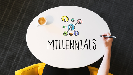 Millennials text on a white table with person?s hand Stock Photo