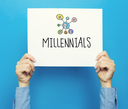 hand holding paper: Millennials text on a white poster on a blue background Stock Photo