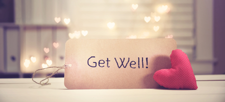 Get Well message with a red heart with heart shaped lights Stock Photo