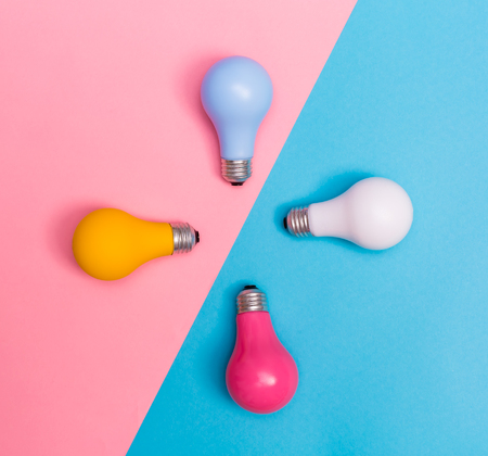 Colored light bulbs on a blue and pink background Stock Photo