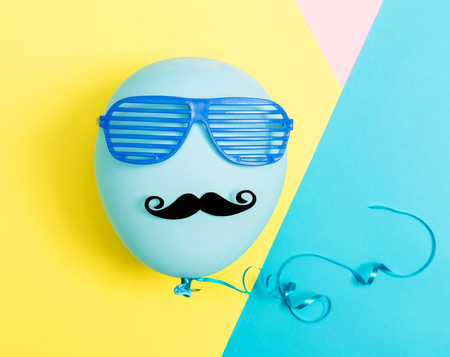 Party theme with balloon, moustache and shutter shades on a vibrant colored background Stock Photo - 78340141
