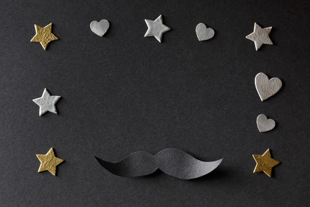 Paper black mustache with small hearts and stars on black paper background