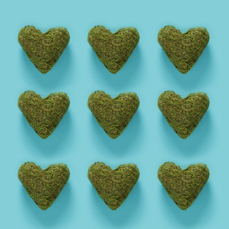 Series of green moss hearts on a blue background