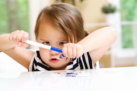 青色のマーカーで遊ぶ幼児の女の子