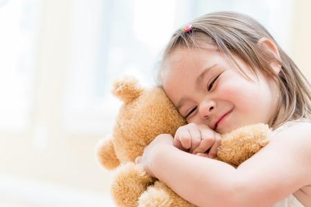 家でクマのぬいぐるみを持つ少女 写真素材