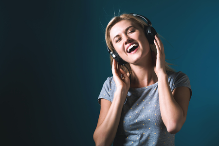 Happy young woman with headphones on a dark blue background