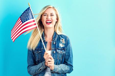 Happy young woman holding American flag Фото со стока