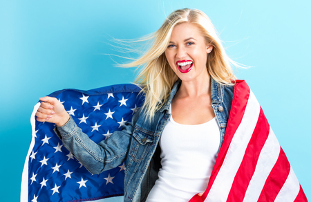 Happy young woman holding American flag Stock Photo