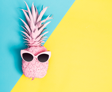 Painted pineapple with sunglasses on a vibrant duotone background 免版税图像